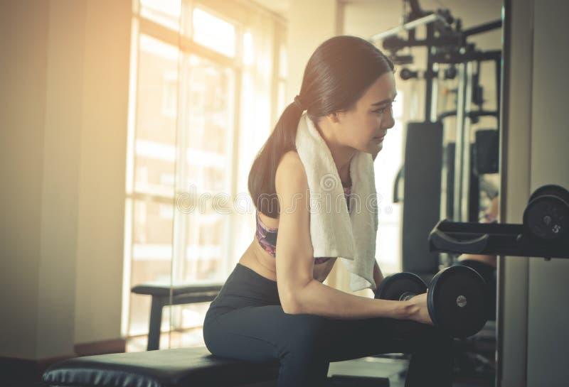 La mujer asiática fuerte está levantando pesa de gimnasia en aptitud fotos de archivo libres de regalías