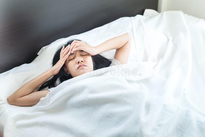 La mujer asiática hace que un dolor de cabeza en cama después de despierte en la mañana foto de archivo libre de regalías
