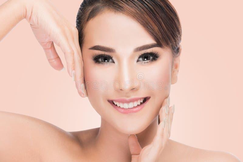 La mujer asiática hermosa cuida para la cara de la piel, mujer hermosa del balneario que toca su cara imagenes de archivo