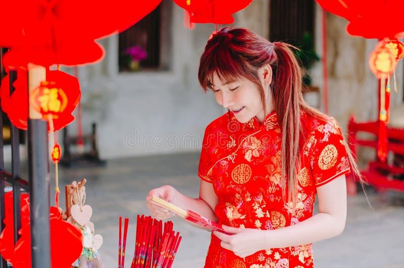 La mujer asiática hermosa encantadora del retrato lleva el cheongsam para vestirse para arriba para elegir comprar el incienso, e fotos de archivo