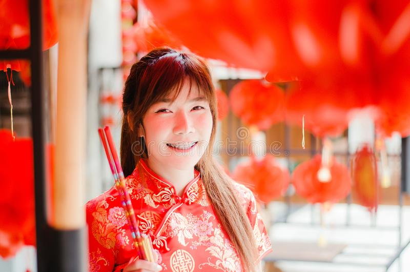 La mujer asiática hermosa encantadora del retrato lleva el cheongsam para vestirse para arriba para elegir comprar el incienso, e fotografía de archivo