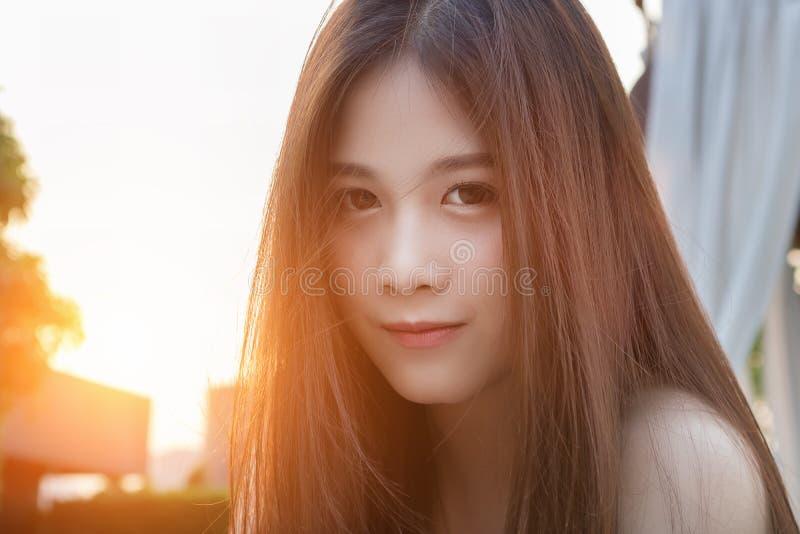La mujer asiática hermosa es feliz en la puesta del sol foto de archivo libre de regalías