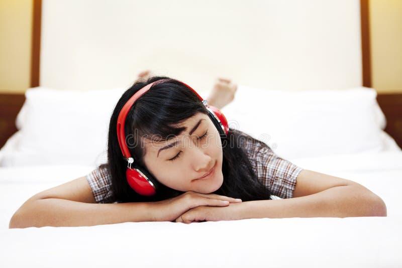 La mujer asiática hermosa escucha una música en cama imagen de archivo