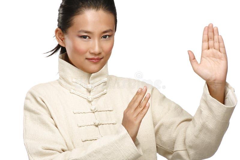 La mujer asiática hermosa hace gesto del kung-fu foto de archivo