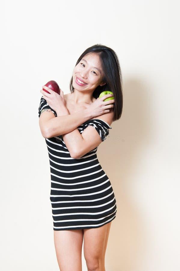 La mujer asiática hermosa joven sonriente muestra el backg del blanco de dos manzanas fotografía de archivo