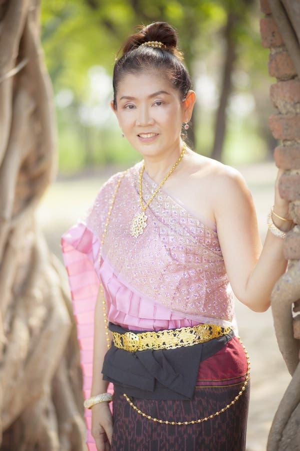 La mujer asiática hermosa que lleva la tradición tailandesa viste el smil dentudo fotografía de archivo libre de regalías