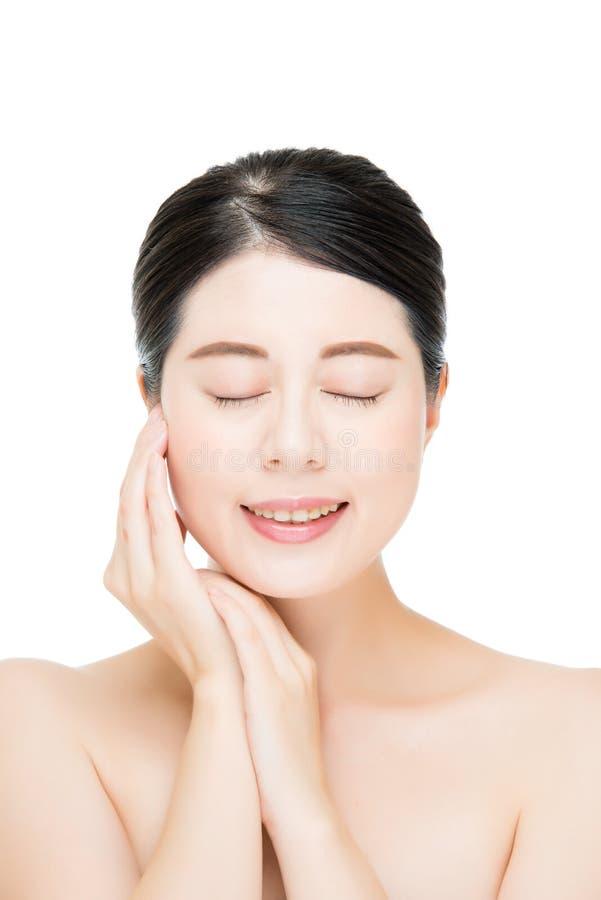 La mujer asiática hermosa toca su cara de la belleza, fondo blanco foto de archivo