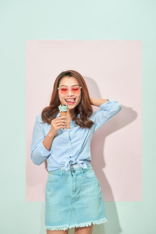 La mujer asiática joven con sonrisa dentuda sostiene el helado sabroso, soportes en fondo rosa claro fotos de archivo