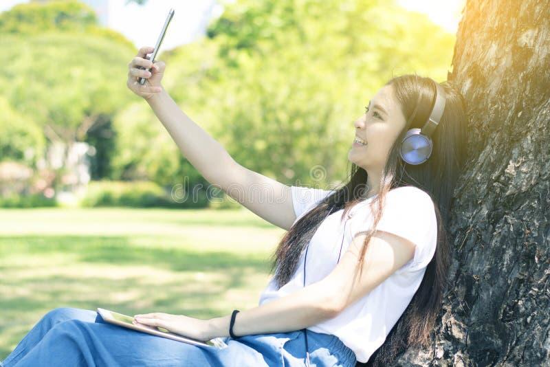 La mujer asiática joven debe disfrutar de forma de vida escuchando la música y del selfie en el mismo tiempo fotos de archivo libres de regalías