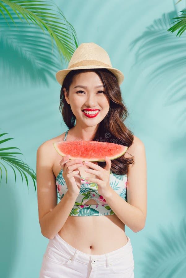 La mujer asiática joven feliz del retrato está llevando a cabo la rebanada de sandía foto de archivo