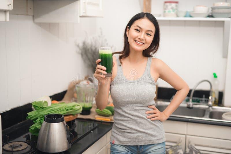 La mujer asiática joven goza del smoothie vegetariano sano para el peso l fotografía de archivo