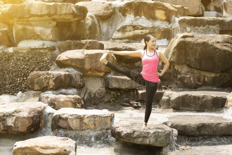 La mujer asiática joven hermosa es yoga del ejercicio del entrenamiento en el parque foto de archivo