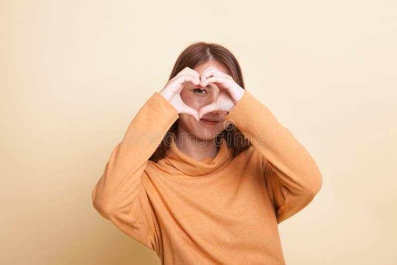 La mujer asiática joven hermosa hace la muestra de la mano del corazón foto de archivo