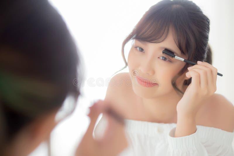 La mujer asiática joven hermosa que aplica el cepillo de las cejas del maquillaje, muchacha de Asia de la belleza que usa el cosm imagen de archivo