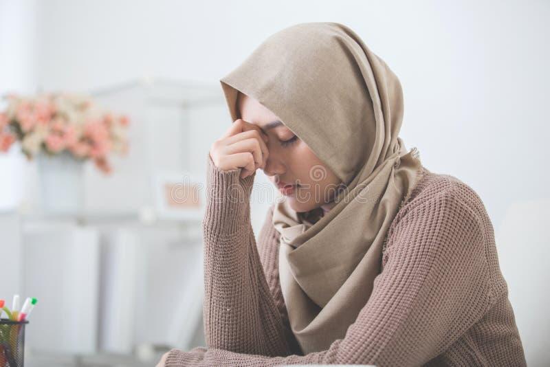 La mujer asiática joven lleva a cabo a su cabeza que piensa en algo fotografía de archivo libre de regalías