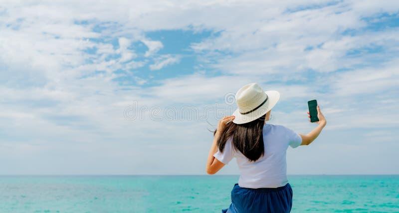 La mujer asiática joven lleva el smartphone del uso del sombrero de paja que toma el selfie en el embarcadero de madera Vacacione foto de archivo libre de regalías