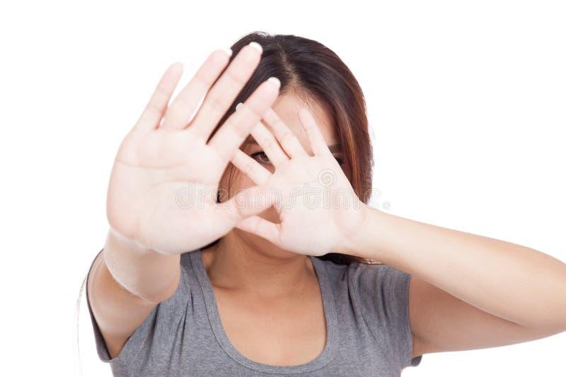 La mujer asiática joven oculta su cara con la mano foto de archivo