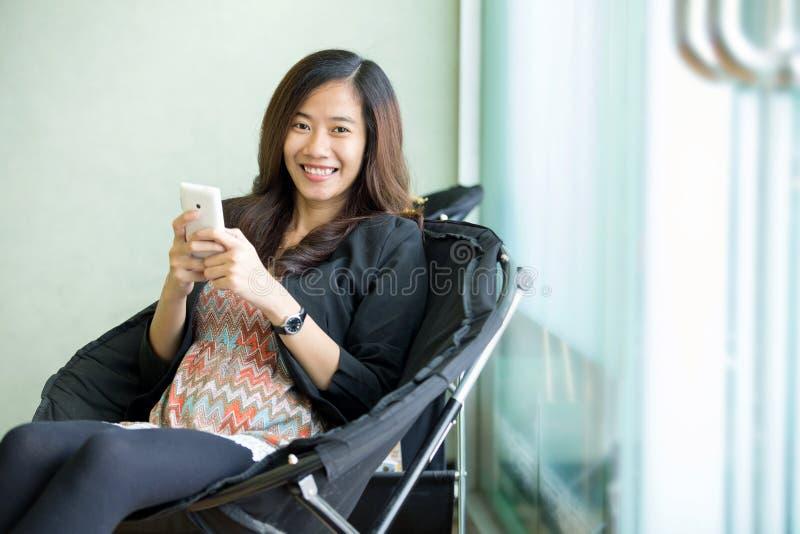 La mujer asiática joven sienta y utiliza su teléfono elegante fotos de archivo