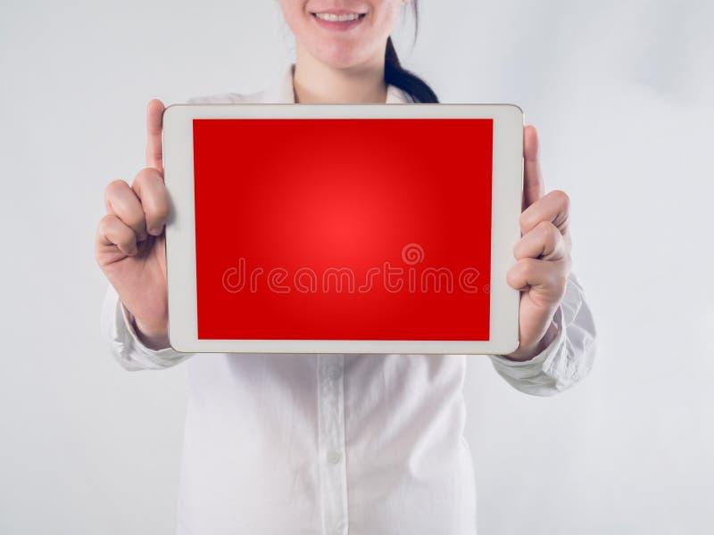 La mujer asiática joven sonriente de la cara con la mano lleva a cabo el backg del rojo de la pendiente fotos de archivo