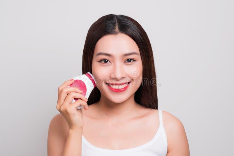 La mujer asiática joven utiliza un cepillo eléctrico para profundamente limpio imagen de archivo