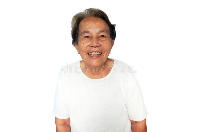 La mujer asiática mayor es sonrisas aislada en blanco imagen de archivo