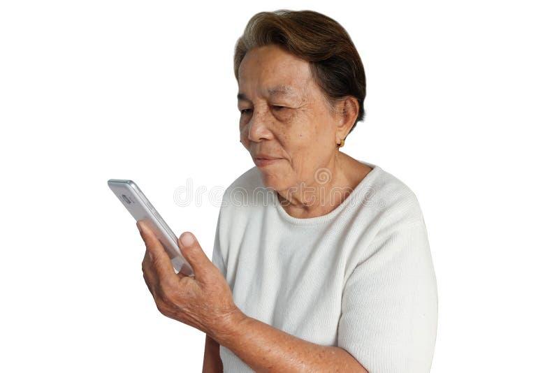 La mujer asiática mayor está utilizando el teléfono móvil con una sonrisa aislado en blanco fotografía de archivo libre de regalías
