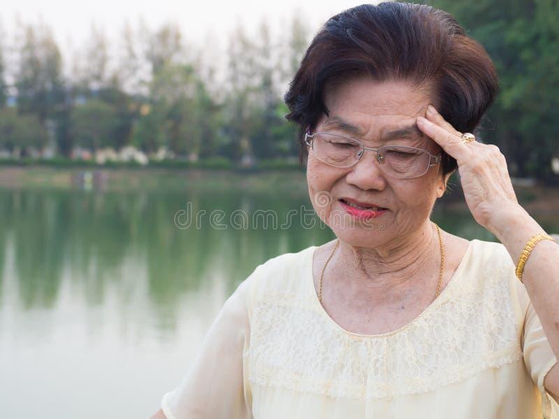 La mujer asiática mayor llevó vidrios ella no era cómoda con dolores de cabeza Cuando mujer mayor que camina en el parque fotos de archivo libres de regalías
