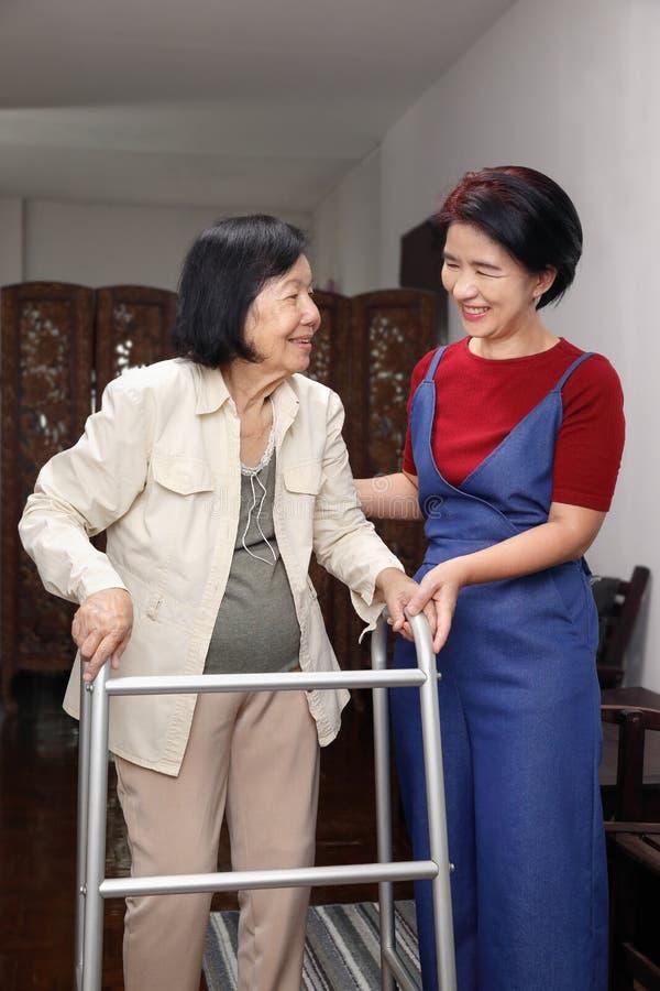 La mujer asiática mayor que usa al caminante con la hija toma cuidado foto de archivo libre de regalías