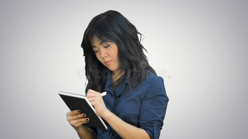 La mujer asiática pensativa hace algunas notas en libreta en el fondo blanco imagenes de archivo