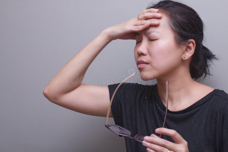 La mujer asiática que lleva a cabo su cabeza, sufre de tener un dolor de cabeza y una fiebre fuertes, vista pobre, hipermetropía, imagen de archivo libre de regalías