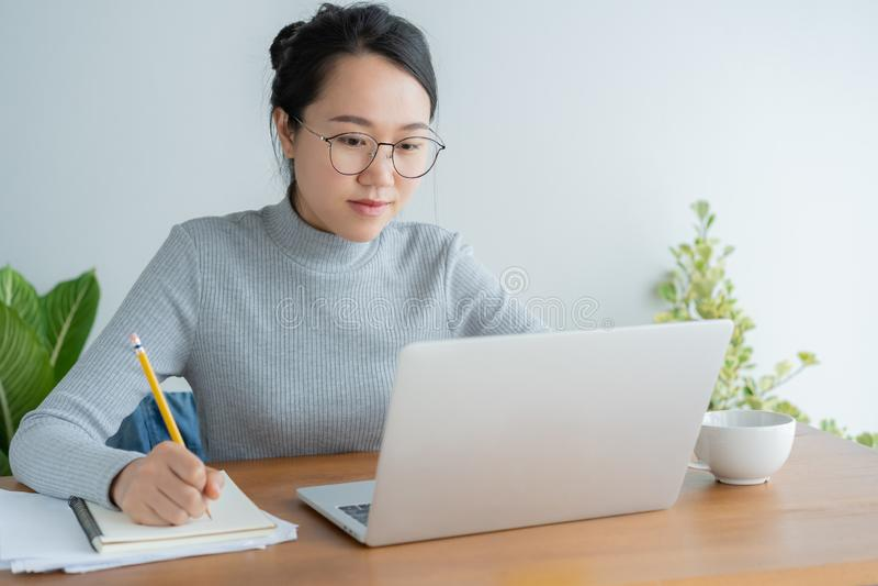 La mujer asiática que lleva los vidrios está utilizando la oficina del ordenador portátil en casa Estudiante lindo joven del retr imagen de archivo libre de regalías
