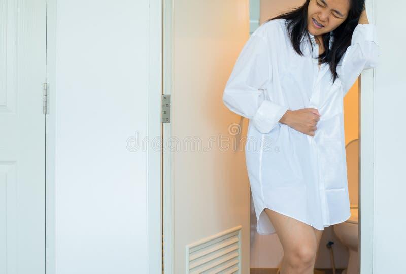 La mujer asiática que usa el retrete y sufre de diarrea y los hemorroides despiertan después por mañana en la casa imágenes de archivo libres de regalías