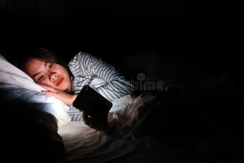 La mujer asiática que usa smartphone en la noche en la cama en sitio oscuro, usando smartphone en oscuridad puede ser causas del  imagen de archivo