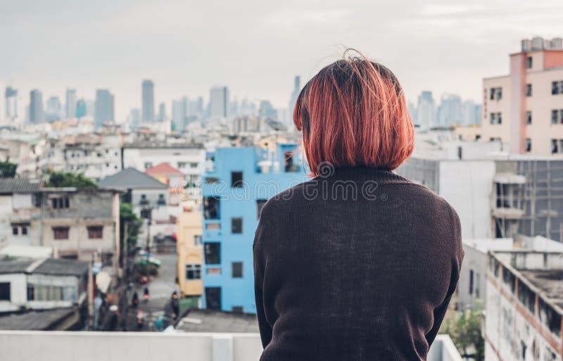 La mujer asiática sola que se sienta en el tejado del edificio ve el paisaje urbano v imágenes de archivo libres de regalías