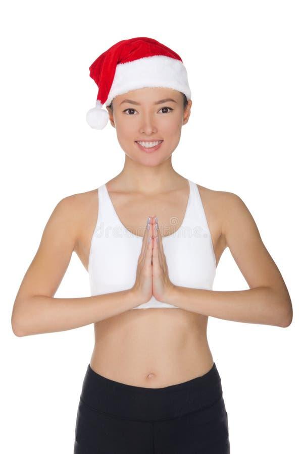 La mujer asiática sonriente en sombrero del ` s de Papá Noel enganchó a aptitud imagen de archivo libre de regalías