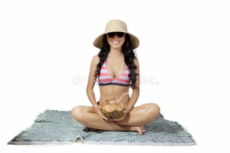 La mujer asiática sostiene un coco en la estera imagen de archivo