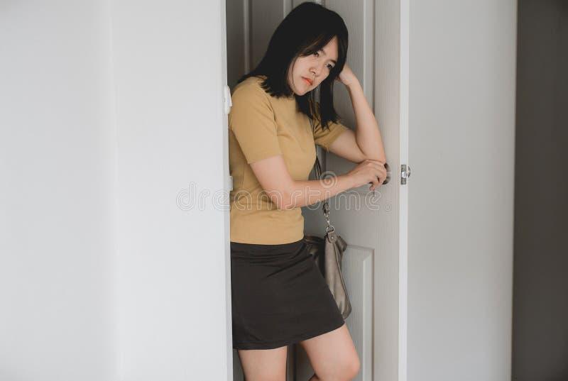 La mujer asiática tiene un dolor de cabeza antes de ir a trabajar por la mañana fotografía de archivo