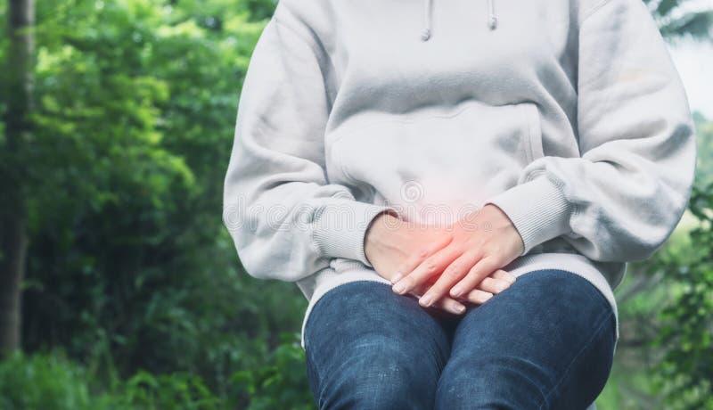 La mujer asiática tiene un dolor de la vejiga o el dolor del uti después de despierta por la mañana imágenes de archivo libres de regalías