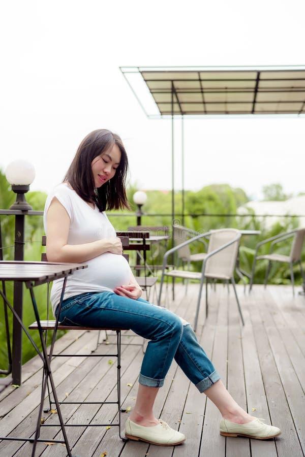 la mujer asi?tica bonita est? embarazada Llevando una camisa blanca siéntese cómodamente y relájese en el balcón de la casa feliz fotos de archivo