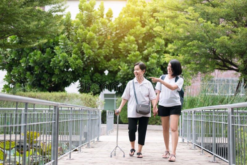 La mujer asi?tica mayor de la tentativa que camina para hacer entrenamiento con el palillo en el parque p?blico, hija toma cuidad fotos de archivo