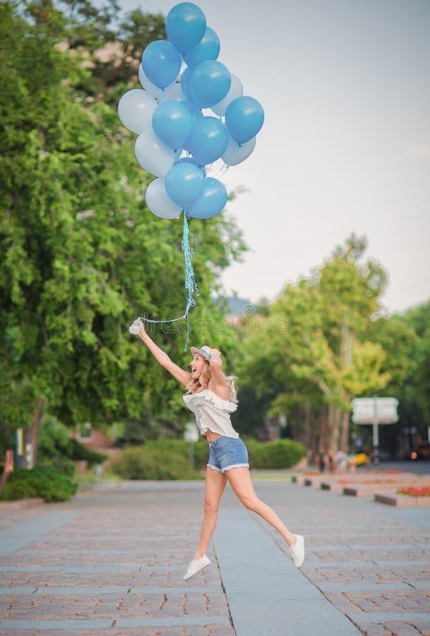 La mujer asombrosa dejó muchos globos azules en el cielo imagenes de archivo