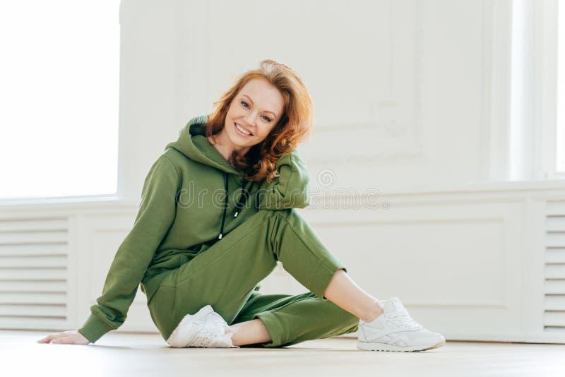 La mujer astuta feliz encantada ocupada con estirar los ejercicios de pilate en estudio de la aptitud, lleva la ropa de deportes, imagen de archivo
