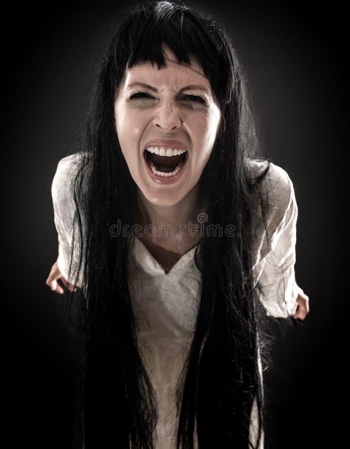 La mujer asustadiza sangrienta loca del zombi grita en la cámara foto de archivo