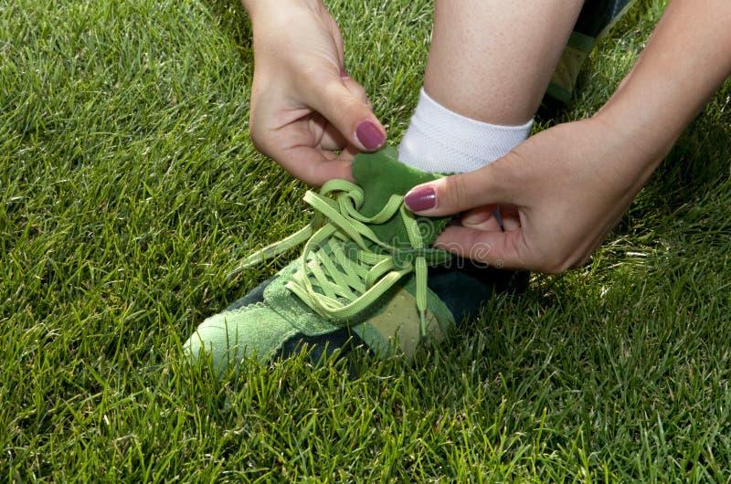La mujer ata cordones en los zapatos verdes imagen de archivo libre de regalías