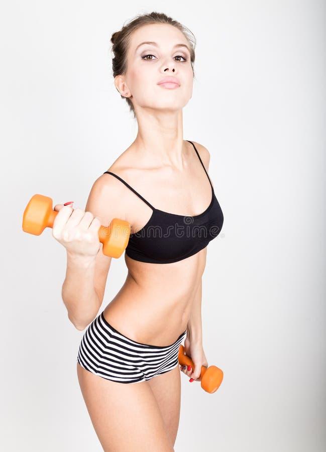 La mujer atlética activa con las pesas de gimnasia que bombean para arriba muscles el bíceps Concepto de la aptitud imagenes de archivo