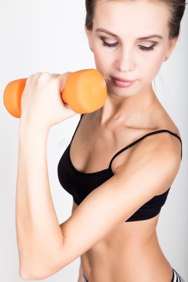 La mujer atlética activa con las pesas de gimnasia que bombean para arriba muscles el bíceps Concepto de la aptitud imagen de archivo libre de regalías