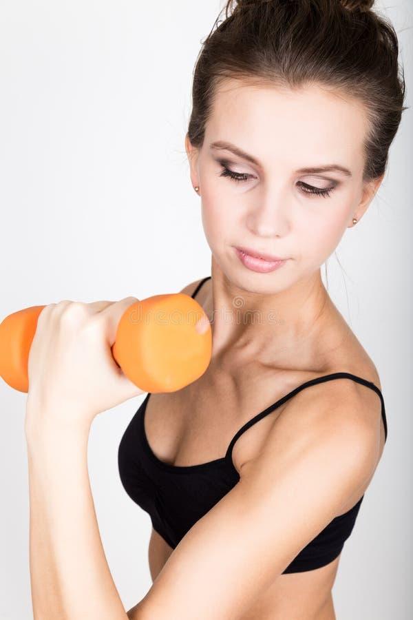 La mujer atlética activa con las pesas de gimnasia que bombean para arriba muscles el bíceps Concepto de la aptitud fotos de archivo libres de regalías