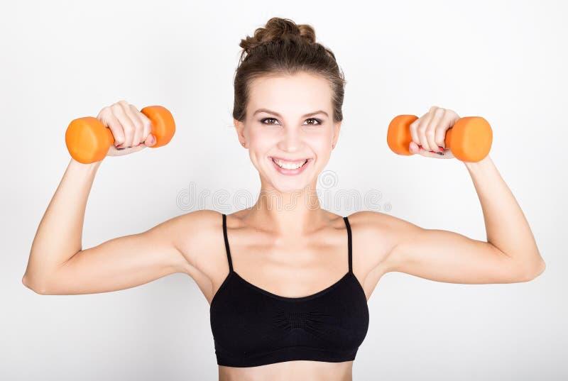 La mujer atlética activa con las pesas de gimnasia que bombean para arriba muscles el bíceps Concepto de la aptitud fotografía de archivo libre de regalías