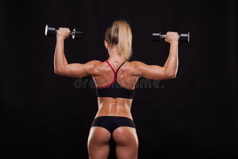 La mujer atlética atractiva está bombeando para arriba muscles con las pesas de gimnasia, visión trasera aislada en fondo oscuro  imagen de archivo