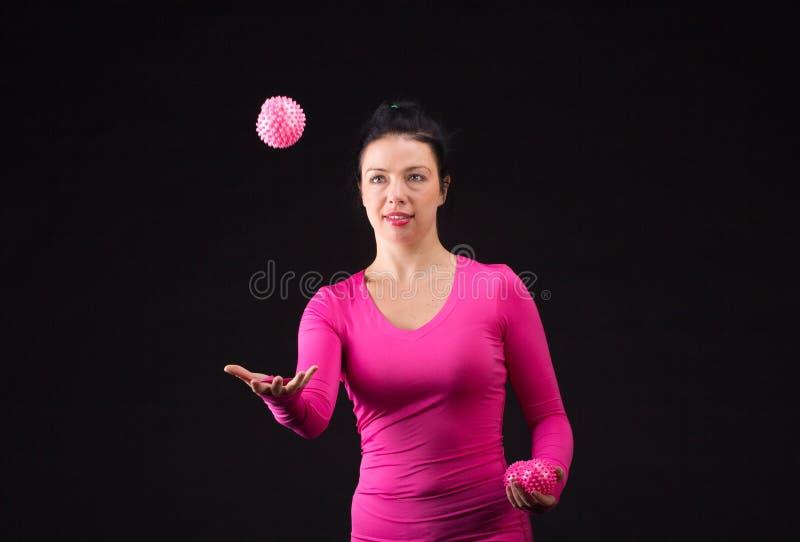 La mujer atlética brutal juega la bola en negro fotos de archivo